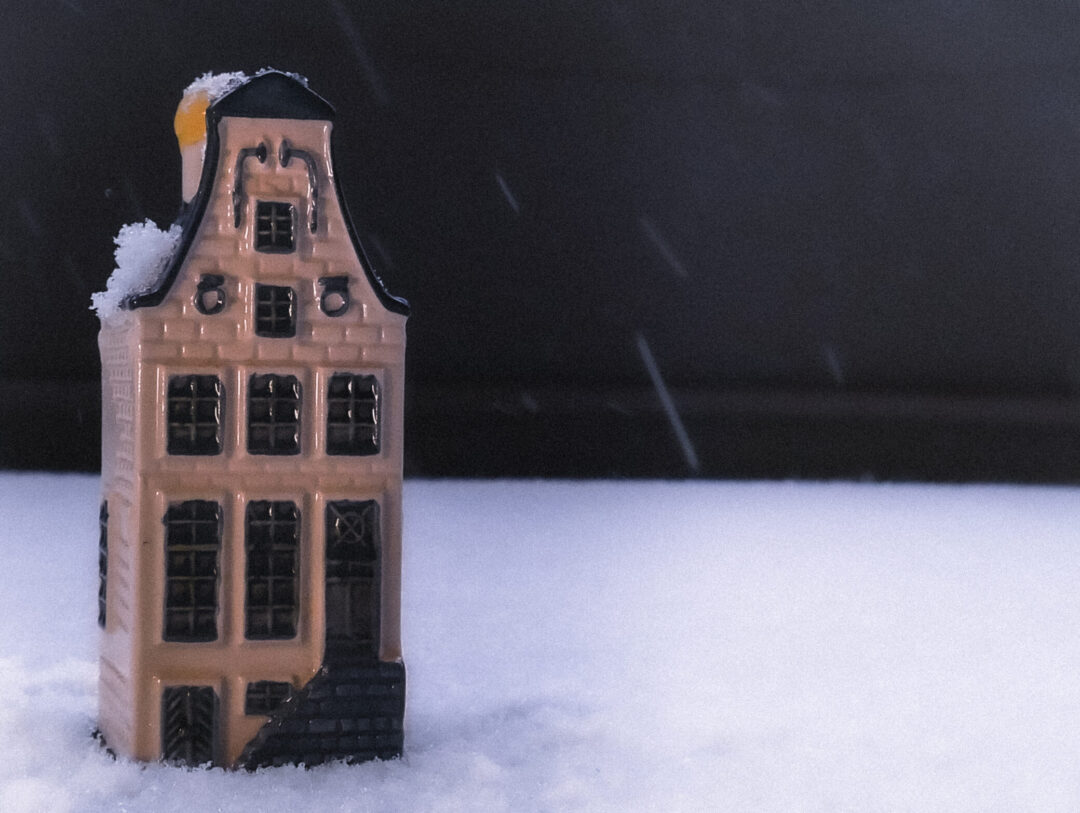 A toy house in a snowy field.