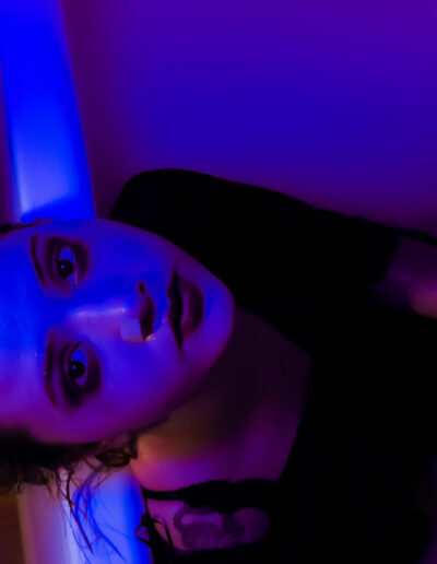 Photo of a classy lady in a white bath. A UV light illuminating the scene.