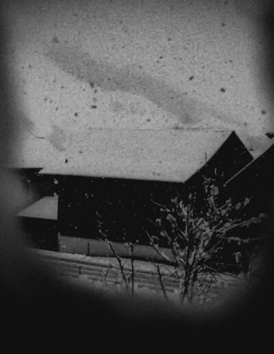 A swiss house in winter photographed through a hole in the snow.
