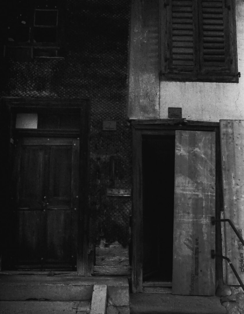 Monochrome photo of a worn down house. on side black and one side white.