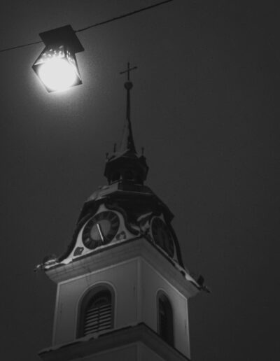 Photo of a swiss church tower at night.