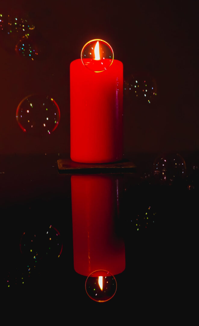 Photo achieved with a fast shutter-speed. The soap bubbles captured perfectly as it descents past the candle flame.