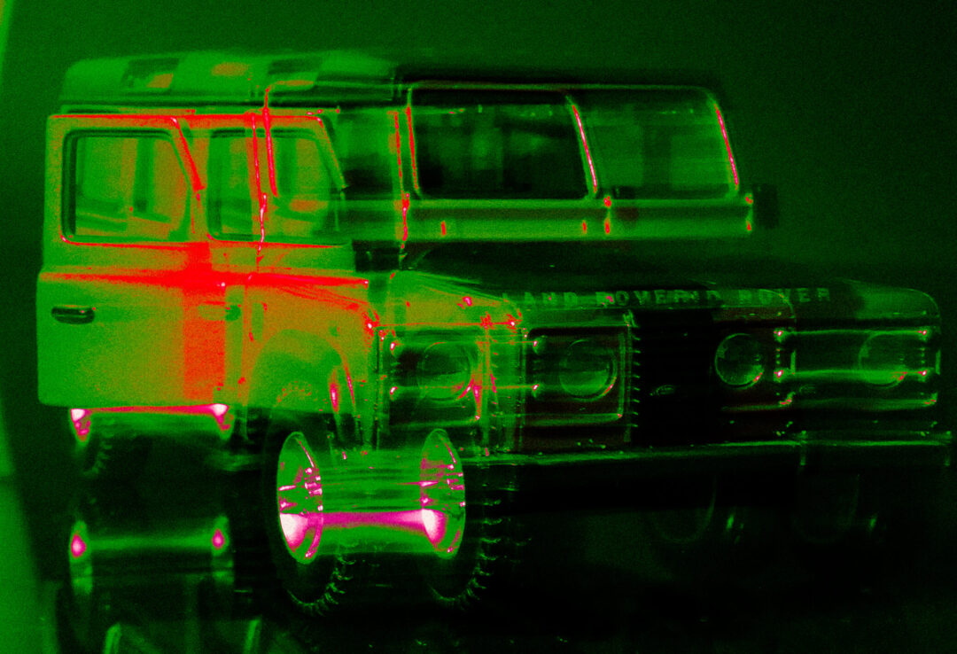 Green photo of a toy Land Rover. Disturtion achieved through a slow shutter-speed.