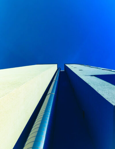 Photo of a tower with two sides. The blue sky hovering overhead.
