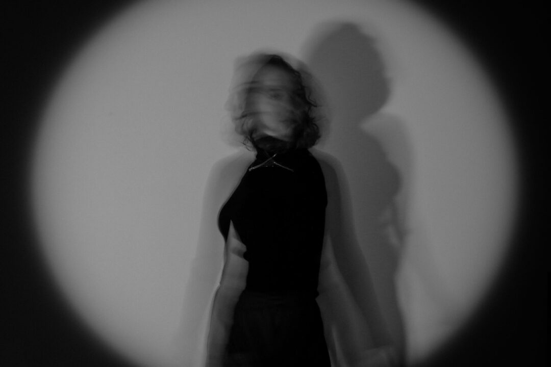 A Monochrome Photo of a Lady. A black Vignette effect surrounding her. Shot with a slow shutter-speed.