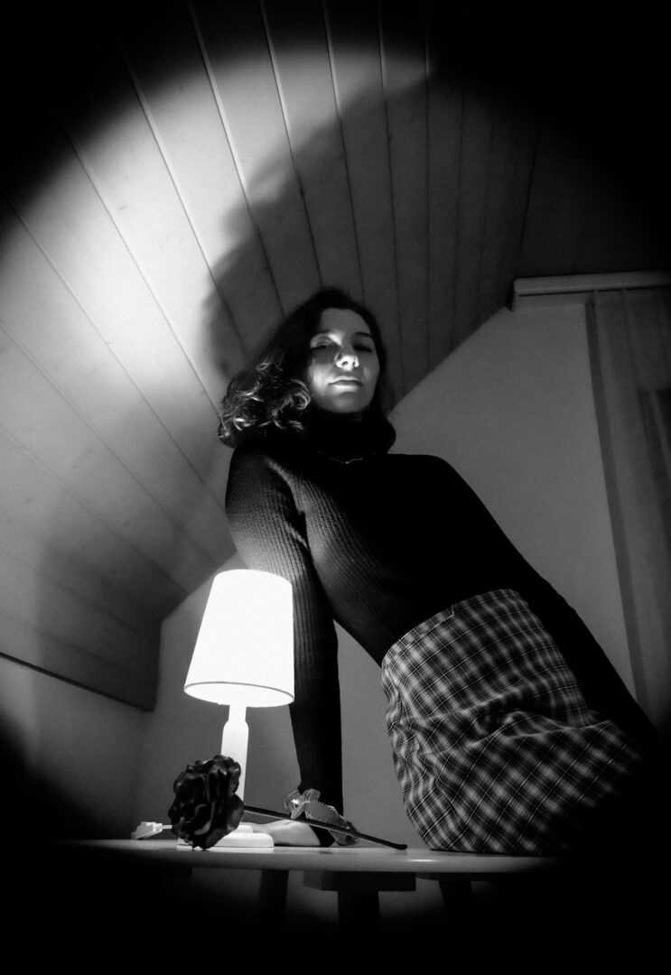 A Monochrome Photo of a Lady. A black Vignette effect surrounding her.