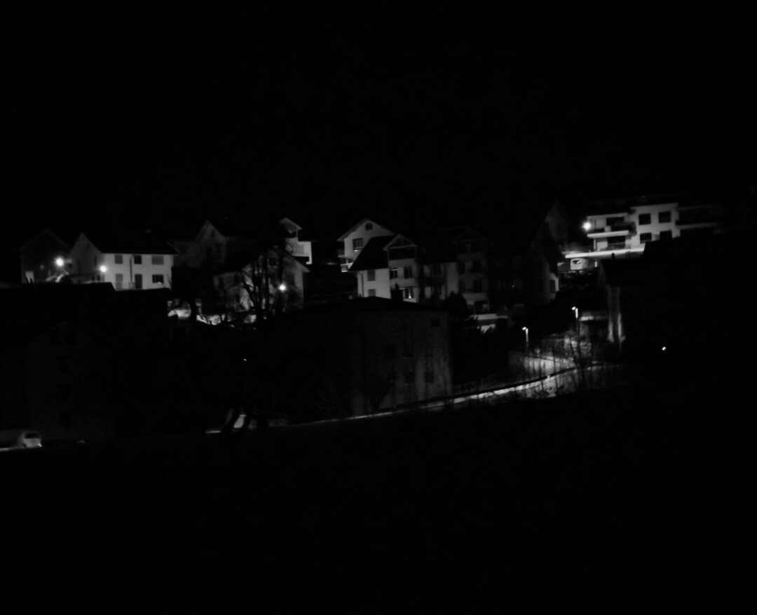 A dark and Monochrome image of a small village in switzerland at 3am. It is visualising the silence and emptines. If it weren't for the few lights it could be a ghosttown.