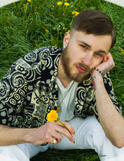 A guy in a field of yellow flowers. wearing vintage clothes and set on a sunny day.